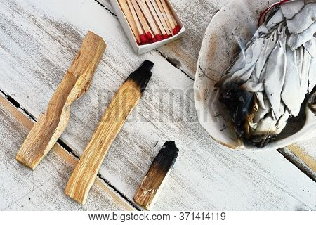 A Top View Image Of Burnt Palo Santo Smudge Sticks On A White Wooden Table Top.
