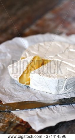 Camembert Cheese In White Paper. Fresh Camembert Cheese.