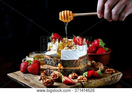 Selective Focus. Honey Flowing With Honey Stick On Camembert Cheese. Camembert Cheese With Nuts, Hon