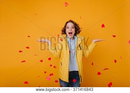 Pleased Caucasian Girl In Stylish Yellow Jacket Expressing Happiness In Valentines Day. Cheerful Fem