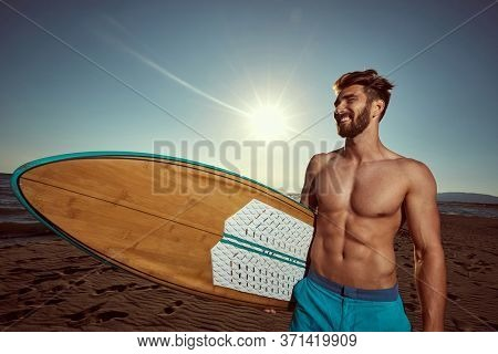 Handsome Man surfer on a beach. Smiling surf man go to surfing.