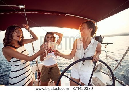 Happy woman drinking on a yacht and enjoying at vacation and luxury travel at sunset.