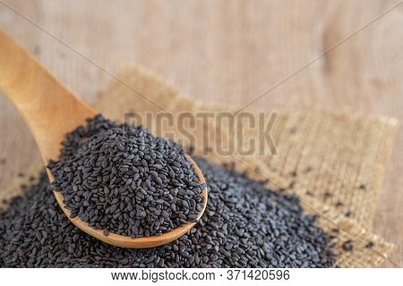 Black Dired Sesame Seeds In Wooden Spoon On Sesame Seeds Stack Over Burlap Fabric On Wooden Panel.