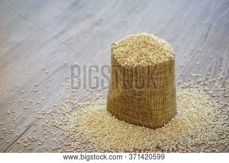 White Dired Sesame Seeds In Burlap Fabric Bag On Sesame Seeds Stack Over Wooden Panel.