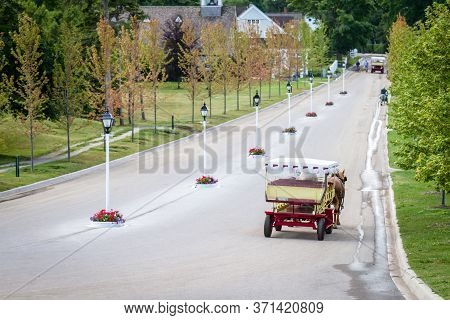 Horse Pulling Wagon Down Long Road On Mackinac Island, Mi