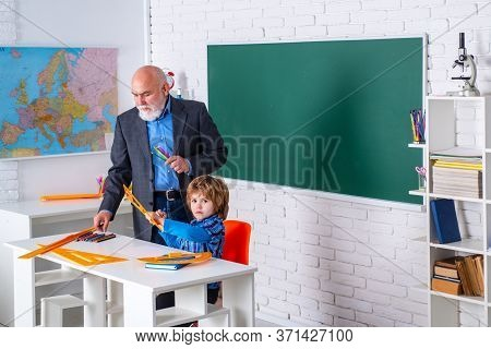 World Teachers Day. Happy Son And Grandfather Sitting At A Desk Indoors. Educational Process. Grandf