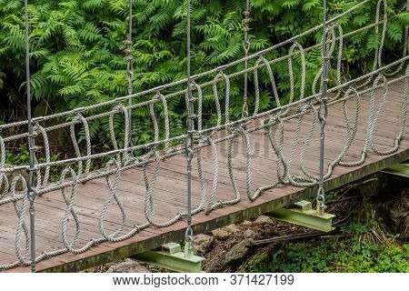 Closeup Of Wood And Rope Bridge Spanning A Ravine In Recreational Forest.