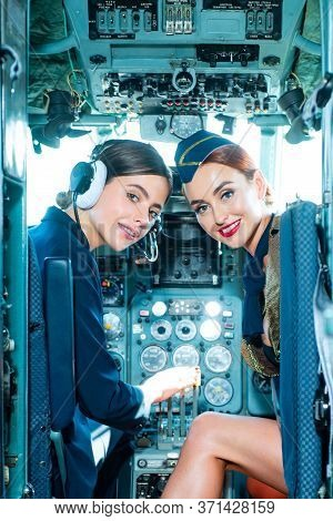 Two Beautiful Women Pilot Wearing Uniform. Looking At Camera Through The Cockpit. Pilots In Cockpit.
