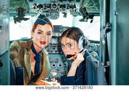 Trainee Pilot And Flight Instructor In An Aircraft Cockpit. Wishes A Successful Flight. Young Girls