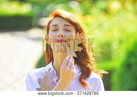 Cheerful Smiling Ginger Woman Holding Fall Oak Leaves. Healthy And Natural Woman Beauty. Fall Woman