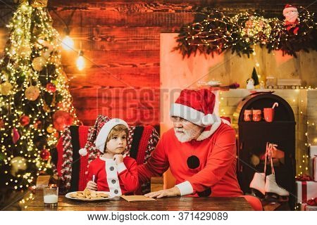 Child Write Letter To Santa. Kid Grandson And Grandfather In Santa Hat Writing Wish List - Unfocused