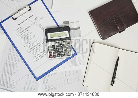 Calculating Export Import Cost. Stack Of Statistic Data, Calculator And Notepad. Detailed Reviewing