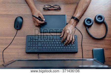 A Man Creates A Design On A Graphic Tablet. He Holds A Stylus In His Hand. Top View. Flat Lay With H