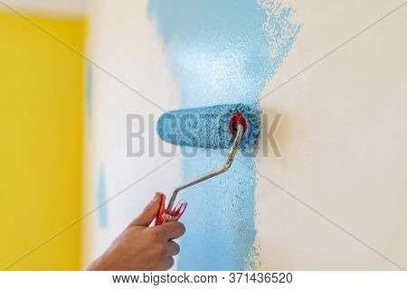 Decorator's Hand Painting Wall With Roller At Indoor.