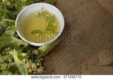 Tea From Linden. Fresh Flowering Linden On A Wooden Background. Healthy And Natural Tea. June Linden