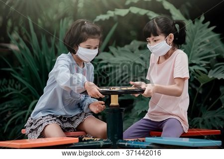 Two Asian Girl Kids Wearing A Mask Playing With A Carousel And Having Fun In The Garden.