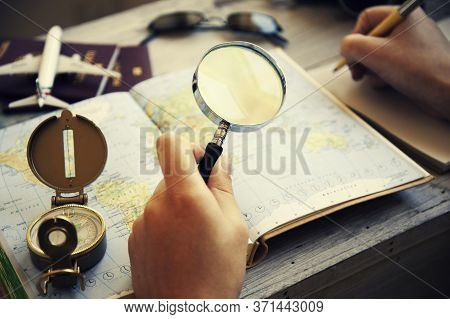 Young Woman Planning Her Vacation With Travel Map. She's Looking For Next Destination With Magnifyin