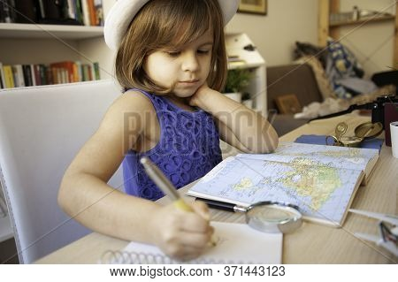 Trendy Little Girl In Summer Casual Wear And White Hat Is Doing  Homework Or Writing Notes, She Cons