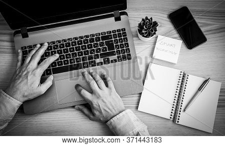 Male Hands Working On Modern Laptop. Working At Home On The Desk With Laptop, Agenda, Pen, Post It A