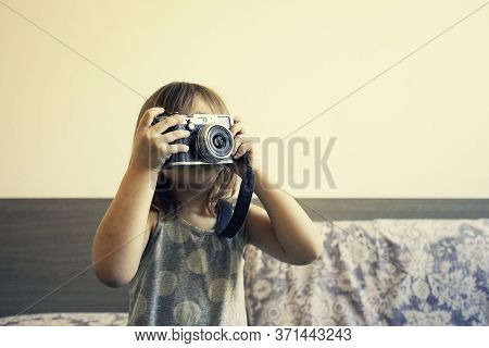 Indoor Lifestyle Portrait Of Cute Little Girl Making Photo. Talented Little Girl Has Fun With Vintag