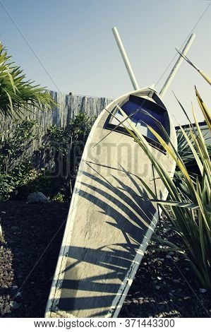Wooden Canoe Leaning Against The Straw Fence With Paddles Crossed. Vintage Canoe Against Blue Sky. V