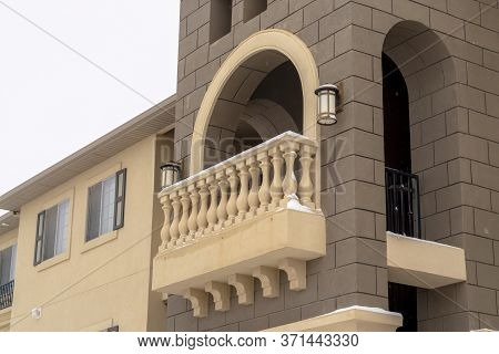 Exterior Of Apartment With Moulded White Balustrade On The Arched Balcony