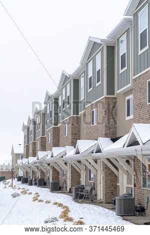 Townhome Facade With Snowy Gabled Roof At The Entrance In Winter