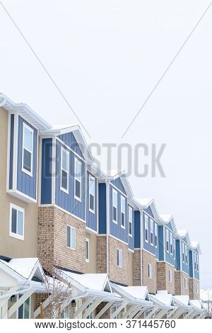 Snowy Gable Roofs At The Facade Of Townhome With Brick Wall And Vertical Siding