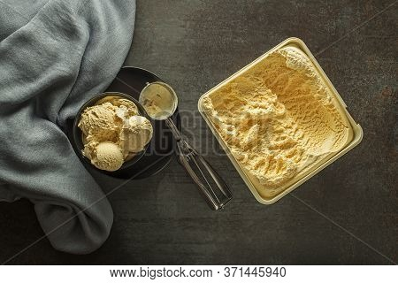 Fresh Of Vanilla Ice Cream Scoops, Scooped Out Of Container In To Bowl With A Silver Utensil
