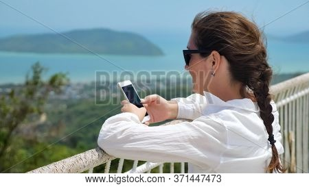 Young Woman Types On Modern Smartphone Leaning On Viewpoint White Handrails Against Pictorial Blurry