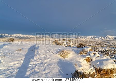 Snowy Hilltop Over Looking Utah Vally Community And Mountain Against Blue Sky