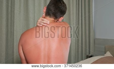 Handsome Guy Touches Red Sunburned Back And Suffers With Pain Sitting In Bedroom Closeup