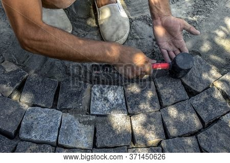 A Man Holds A Red-black Rubber Mallet In His Hand And Knocks It On The Surface Of Gray Granite Stone