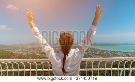 Woman In White Blouse Raises Hands Admiring Picturesque Landscape With Blue Ocean Standing On Hillto