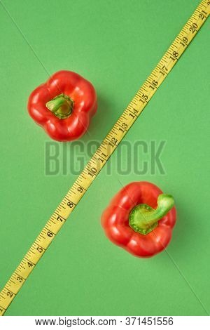 Creative composition from two red paprika pepper and diagonal yellow measuring tape as the symbol of percent on a green background, copy space. Top view. Low calorie food for reduction of weight.