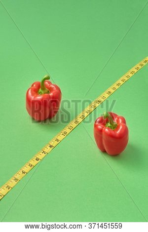 Healthy set from two red paprika pepper and diagonal yellow measuring tape as the sign of percent on a green background, copy space. Low calorie food for reduction of weight.