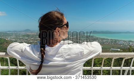 Brunette In Sunglasses Admires Pictorial Tropical Cityscape And Ocean Bay On Observation Deck Under