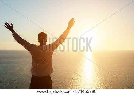 Male Silhouette Raises Hands And Admires Pictorial Sunset Standing On Beach Edge At Sunset Copyspace