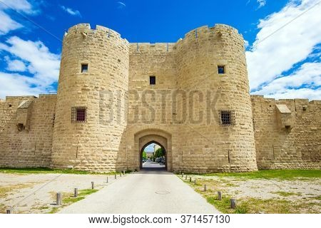 Picturesque powerful fortifications and gates defend the port city of Aigues-Mortes. Around the walls are green lawns.  The concept of historical and photo tourism