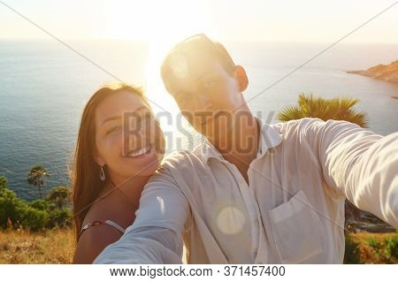 Couple Makes Selfie And Lady In Summer Dress Hugs And Kisses Guy Against Endless Blue Ocean Under Br