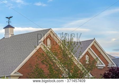 Weather Vane And Vent On Top Of The Gray Gable Roof Of Home Against Blue Sky