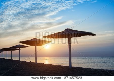 Sunbeds And Umbrella On The Beach At Sunset By The Sea. Beautiful Concept For Vacation, Summer Holid