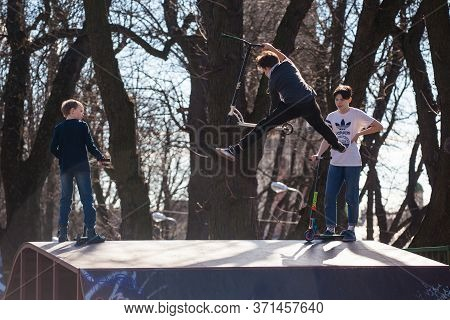 Lviv, Ukraine - March 12, 2020: Kids Ride On Scooter At Skate Park. Young Boy Going Airborne With Hi