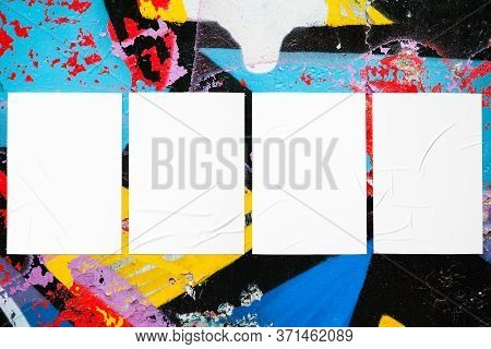 Closeup of colorful messy painted urban wall texture with four wrinkled glued poster templates. Modern mockup for design presentation with clipping path. Creative urban city background.
