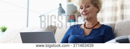 Elderly Woman Sitting With Laptop On Her Lap Home. Informational Research. Desire To Study And Havin