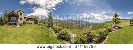 Panorama Of The Backyard Of Home With Landscaped Grassy Lawn And Lush Plants