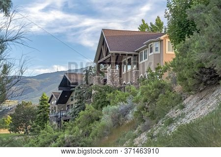 Homes On Hilly Terrain With Mountain And Cloudy Blue Sky In The Background