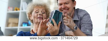Elderly Mother Shows Photo In Phone To Adult Son. Adult Mother Shows Her Son His Page On Social Netw
