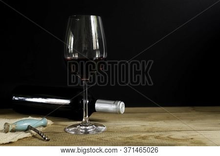 Red Wine Bottle Lying Down, Red Wine Glass And Old Corkscrew