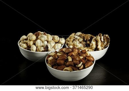 Three White Ceramic Bowls With Hazelnuts , Walnuts  And Peanuts